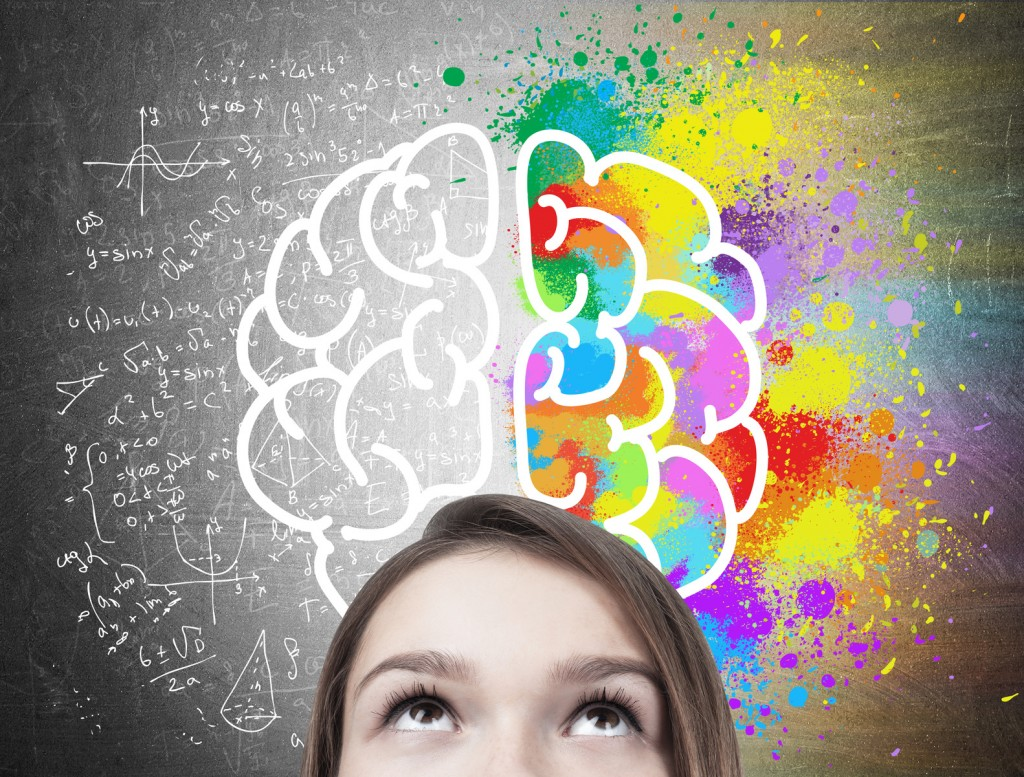 Close up of a blond teen girl s head near a blackboard with a colorful brain sketch drawn on top of formulae.